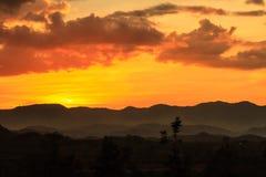 Sumário mostrado em silhueta do por do sol dos mountians Fotografia de Stock