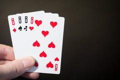 Sumário: o homem que a mão que guarda o cartão de jogo quatro oito se isolou no fundo preto com pôquer do copyspace ajustou quatr Fotografia de Stock Royalty Free