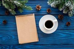 Suma w górę roku Notatnik i kawowa pobliska świerczyna rozgałęziamy się na błękitnym drewnianym tło odgórnego widoku mockup Zdjęcia Royalty Free
