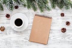 Suma w górę roku Notatnik i kawowa pobliska świerczyna rozgałęziamy się na lekkim drewnianym tło odgórnego widoku mockup Zdjęcie Royalty Free