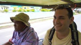 Sumatra, Indonesia - 20 JUNE 2016; Caucasian tourist ride local Asian transport. Sumatra, Indonesia - 20 JUNE 2016 Caucasian tourist ride in local Asian stock footage