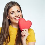Sumbol of love. Smiling woman holding heart. Sumbol of love. Close up face portrait of Smiling woman holding heart. Isolated portrait of beautiful girl with Stock Photography