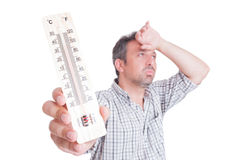 Sumer heat and heatwave concept with man holding thermometer Stock Images
