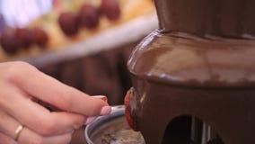Sumergiendo el pincho de la fruta en llover la fuente de la 'fondue' de chocolate almacen de video