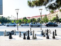 Sumgait, Azerbaijan - July 19, 2018: Outdoor chess board with big plastic pieces. cars royalty free stock photography