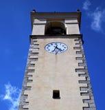 Sumirago i Italien väggen och det kyrkliga tornet sätter en klocka på soligt D Arkivbild