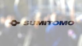 Sumitomo Corporation logo on a glass against blurred crowd on the steet. Editorial 3D rendering. Sumitomo Corporation logo on a glass against blurred crowd on stock video