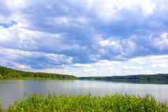 Summer湖在一个晴天 森林很远 美丽的蓝色覆盖天空日出 免版税库存照片