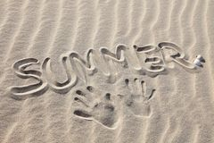 Summer. Writings in the sand on the beach symbolizing summer holiday Stock Photos