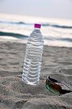 Summer. Water bottle and sun class on beach Stock Photography