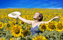 Summer. Young beautiful woman in a sunflower field Royalty Free Stock Image