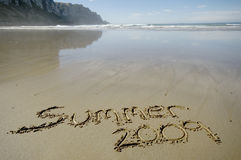 Summer 2009. Written in the sand with background of waves and blue sky Stock Photos