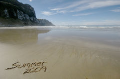 Summer 2009. Written in the sand with waves and blue sky background Royalty Free Stock Image