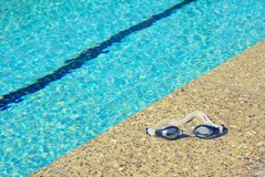 In the Summer. A pair of goggles lay by the side of a pool Stock Photo