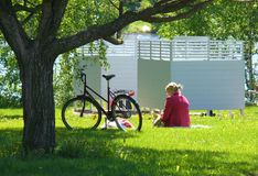 Summer. A woman sitting in the grass at the park on a warm summer day Stock Photography
