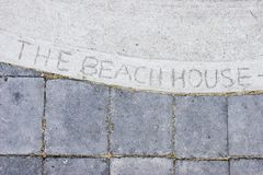 Summer. Entrance to summer beach house with 'the beach house' carved in the concrete stock photo