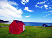 Summer. Day by the sea. Red house/barn in the foreground on a wide field of green grass, set against a brilliant blue sky, with a blue house in the distant Stock Image