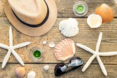 Summer accessories as hat, shells, sun glasses and candles on wo Royalty Free Stock Images