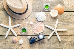 Summer accessories as hat, shells, sun glasses and candles on wo Stock Images