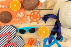 Summer accessories. Beach accessories. Hat, sunscreen, sunglasses, flip flops, and an orange on a natural wooden table. top view stock photography