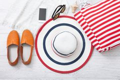 Summer accessories hat and bag on white wooden background. Stock Photos