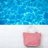 Summer accessories hat and bag on white wooden background. Stock Image