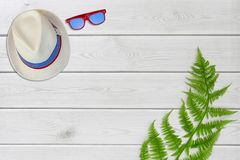 Summer accessories hat, sunglasses on white wooden background. minimal flat lay concept from summertime and holiday trip. Stock Photography