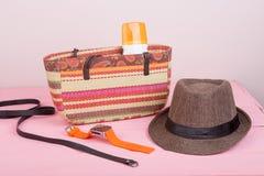 Summer accessories - straw beach bag, sun hat, belt, watch, sunt. Summer accessories - straw beach bag, sun hat, belt, orange watch, suntan lotion on pink wooden Royalty Free Stock Photography
