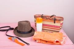 Summer accessories - straw beach bag, sun hat, belt, watch, sunt. An lotion, orange denim shorts on pink wooden table Stock Photos