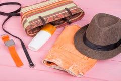 Summer accessories - straw beach bag, sun hat, belt, watch, sunt. An lotion, orange denim shorts on pink wooden table Stock Photography
