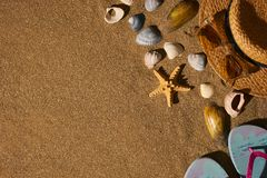 Summer accessories straw hat, glasses, shoes at the beach sand Royalty Free Stock Photography