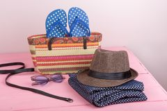 Accessories - sunglasses, straw beach bag, sun hat, belt and flip flops on pink wooden table. Summer accessories - sunglasses, straw beach bag, sun hat, belt and Royalty Free Stock Image