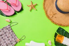 Summer accessories with t-shirt, seashells, flip flops sunscreen bottle and straw hat on green background top view flat lay stock photos