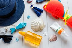 Summer accessories for woman: straw hat, compass, shells, swimsuit, glasses, sun spray, fishes on wooden background. Travel, stock photo