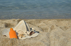 Summer accessorize. Straw hat, sun lotion, glasses and sea star set on a beach with sea in background Stock Image