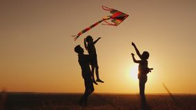 Summer activity - the family plays carefree with a kite royalty free stock image