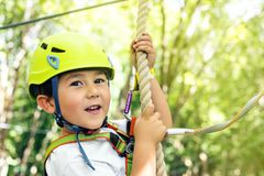 Summer adventure leisure in Albania. Happy little boy passing the cable route high among trees, climbing and playing, extreme sport in adventure park Stock Photo