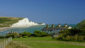 Summer afternoon light on the Severn Sisters white cliffs and the Coast Guard cottages at Cuckmere, in the South Downs National stock photography