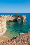 Summer in Algarve coast, Portugal. Rocks in the shoreline and blue water Stock Photography
