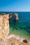 Summer in Algarve coast, Portugal. Rocks in the shoreline and blue water Royalty Free Stock Images