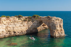Summer in Algarve coast, Portugal. Rocks in the shoreline and blue water Stock Images