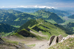 Summer Alpine landscape. Green mountain ridge. Horizon line with some clouds Royalty Free Stock Photos