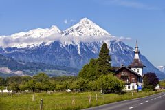 Summer alpine landscape Switzerland with snow peaks and wooden buildings Stock Images