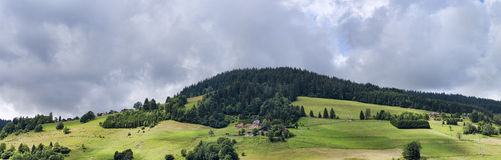 Summer Alpine Panorama with sunny meadow forest and houses stock photography