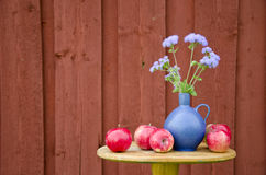 Summer apple fruits and blue vase with flowers Stock Photos