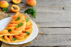 Summer apricot omelette. Omelette stuffed with fresh apricot slices and mint leaves on a white plate Stock Photography