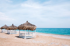 Summer arbor on beach. Summer arbors on beach. Breathtaking view on mediterranean sea. White wooden summerhouses on sunny day. Blue sky and fluffy clouds Stock Photo