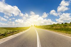 Summer asphalt road in sunrise to the sun. Beautiful yellow field with sun flare effect countryside landscape stock photos