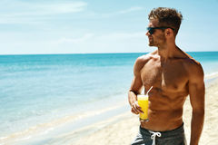 Summer. Athletic Muscular Man Drinking Juice Cocktail On Beach Stock Photography