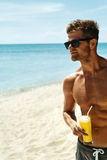 Summer. Athletic Muscular Man Drinking Juice Cocktail On Beach Royalty Free Stock Photography